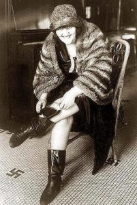 A 1930s flapper stuffing a glass flask into her boot. Hence the term 'bootlegging'. Regarding the swastikas on the tile floor: swastikas did not really convey a political message in the United States at that time. they were seen as 'chic' and slightly provocatory among the flapper/bar scene in the 1920/30s | Photo: Wikimedia Commons
